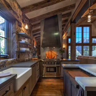 Inspiration for a mid-sized country u-shaped separate kitchen in Denver with a farmhouse sink, shaker cabinets, dark hardwood floors, with island, brown floor, grey benchtop, distressed cabinets, concrete benchtops, brown splashback, stone tile splashback, panelled appliances and exposed beam.