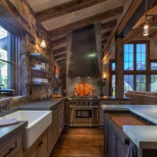 デンバーの中くらいのラスティックスタイルのおしゃれなキッチン (エプロンフロントシンク、シェーカースタイル扉のキャビネット、濃色無垢フローリング、茶色い床、グレーのキッチンカウンター、ヴィンテージ仕上げキャビネット、コンクリートカウンター、茶色いキッチンパネル、石タイルのキッチンパネル、パネルと同色の調理設備、表し梁) の写真