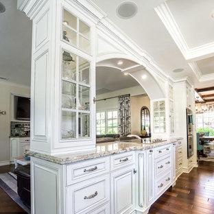 サンディエゴの広いカントリー風おしゃれなキッチン (エプロンフロントシンク、レイズドパネル扉のキャビネット、白いキャビネット、御影石カウンター、ベージュキッチンパネル、トラバーチンのキッチンパネル、シルバーの調理設備、濃色無垢フローリング、茶色い床、マルチカラーのキッチンカウンター) の写真