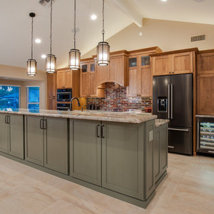 フェニックスの大きいおしゃれなキッチン (ダブルシンク、シェーカースタイル扉のキャビネット、御影石カウンター、赤いキッチンパネル、セラミックタイルのキッチンパネル、黒い調理設備、磁器タイルの床、ベージュの床、緑のキッチンカウンター、中間色木目調キャビネット) の写真