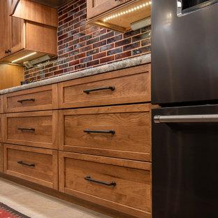 フェニックスの大きいおしゃれなキッチン (ダブルシンク、シェーカースタイル扉のキャビネット、中間色木目調キャビネット、御影石カウンター、赤いキッチンパネル、セラミックタイルのキッチンパネル、黒い調理設備、磁器タイルの床、ベージュの床、緑のキッチンカウンター) の写真