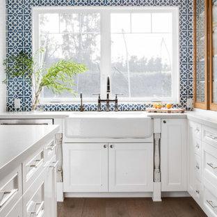 Country Küche in L-Form mit Landhausspüle, Schrankfronten mit vertiefter Füllung, weißen Schränken, Küchenrückwand in Blau, dunklem Holzboden, Kücheninsel, braunem Boden und grauer Arbeitsplatte in Orange County