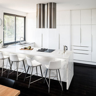 Design ideas for a mid-sized modern u-shaped eat-in kitchen in Melbourne with an integrated sink, flat-panel cabinets, white cabinets, quartz benchtops, black appliances, dark hardwood floors, a peninsula, black floor and yellow benchtop.