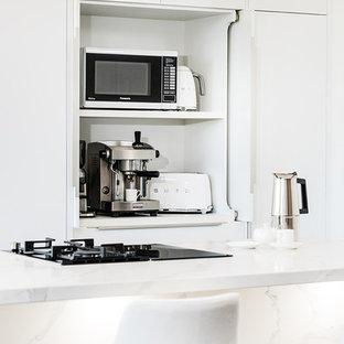 Idee per una cucina minimalista di medie dimensioni con lavello integrato, ante lisce, ante bianche, top in quarzo composito, elettrodomestici neri, parquet scuro, penisola, pavimento nero e top giallo
