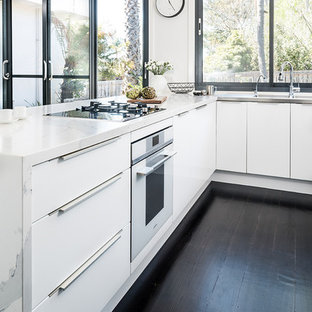 Inspiration for a mid-sized modern u-shaped eat-in kitchen in Melbourne with an integrated sink, flat-panel cabinets, white cabinets, quartz benchtops, black appliances, dark hardwood floors, a peninsula, black floor and yellow benchtop.