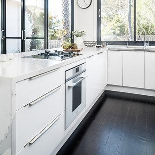 Immagine di una cucina moderna di medie dimensioni con lavello integrato, ante lisce, ante bianche, top in quarzo composito, elettrodomestici neri, parquet scuro, penisola, pavimento nero e top giallo