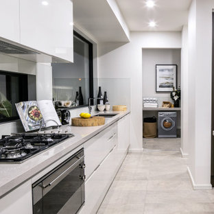 Photo of a large contemporary l-shaped kitchen in Newcastle - Maitland with a double-bowl sink, flat-panel cabinets, white cabinets, window splashback, with island, grey floor and grey benchtop.