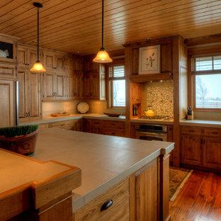Idéer för att renovera ett mellanstort lantligt beige beige kök, med en undermonterad diskho, luckor med upphöjd panel, bruna skåp, kaklad bänkskiva, beige stänkskydd, stänkskydd i porslinskakel, integrerade vitvaror, mellanmörkt trägolv, en köksö och brunt golv