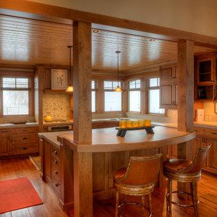 シアトルの中サイズのカントリー風おしゃれなキッチン (アンダーカウンターシンク、レイズドパネル扉のキャビネット、茶色いキャビネット、タイルカウンター、ベージュキッチンパネル、磁器タイルのキッチンパネル、無垢フローリング、ベージュのキッチンカウンター、パネルと同色の調理設備) の写真