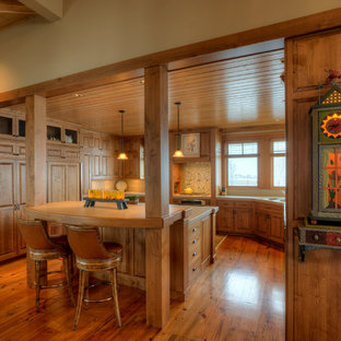 Mid-sized farmhouse enclosed kitchen designs - Mid-sized farmhouse u-shaped medium tone wood floor and brown floor enclosed kitchen photo in Seattle with raised-panel cabinets, medium tone wood cabinets, multicolored backsplash, paneled appliances, an undermount sink, tile countertops and an island