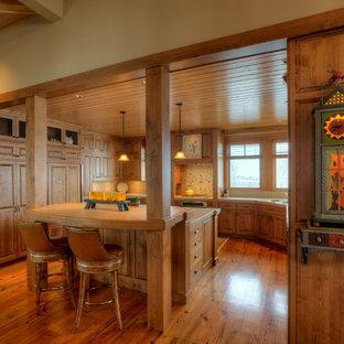 Foto på ett avskilt, mellanstort lantligt u-kök, med luckor med upphöjd panel, skåp i mellenmörkt trä, flerfärgad stänkskydd, integrerade vitvaror, en undermonterad diskho, kaklad bänkskiva, mellanmörkt trägolv, en köksö och brunt golv
