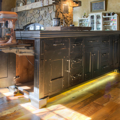 Example of a large mountain style l-shaped medium tone wood floor eat-in kitchen design in Minneapolis with flat-panel cabinets, black cabinets, zinc countertops, paneled appliances, an island and gray countertops