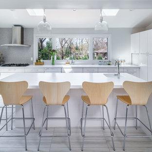 Esempio di una piccola cucina a L moderna con lavello integrato, ante lisce, ante bianche, top in quarzite, paraspruzzi grigio, paraspruzzi con piastrelle a mosaico, elettrodomestici in acciaio inossidabile, pavimento in compensato e un'isola