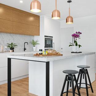 Foto de cocina actual con armarios con paneles lisos, salpicadero de losas de piedra, una isla, puertas de armario de madera oscura, salpicadero verde y suelo de madera clara