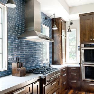 На фото: большая п-образная кухня в стиле современная классика с врезной раковиной, фасадами в стиле шейкер, темными деревянными фасадами, столешницей из бетона, синим фартуком, фартуком из плитки кабанчик, техникой из нержавеющей стали, темным паркетным полом и островом с