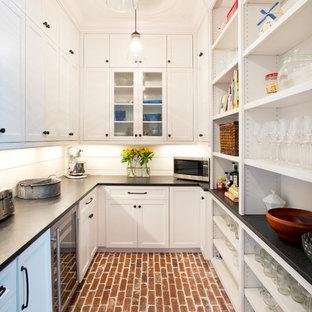 Inredning av ett lantligt kök, med skåp i shakerstil, vita skåp, bänkskiva i täljsten, vitt stänkskydd, svarta vitvaror och tegelgolv
