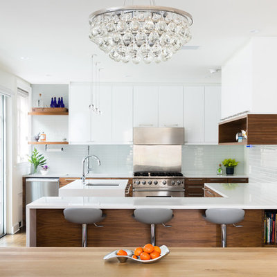 Trendy u-shaped medium tone wood floor and brown floor eat-in kitchen photo in New York with an undermount sink, flat-panel cabinets, medium tone wood cabinets, glass tile backsplash, stainless steel appliances, an island and white countertops