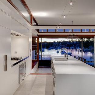 シドニーの中サイズのコンテンポラリースタイルのおしゃれなキッチン (フラットパネル扉のキャビネット、白いキャビネット、シルバーの調理設備の、一体型シンク、白いキッチンパネル、トラバーチンの床) の写真