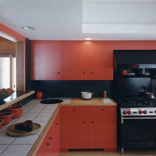バーリントンの中くらいのコンテンポラリースタイルのおしゃれなキッチン (ドロップインシンク、フラットパネル扉のキャビネット、赤いキャビネット、タイルカウンター、黒いキッチンパネル、磁器タイルのキッチンパネル、黒い調理設備、淡色無垢フローリング) の写真