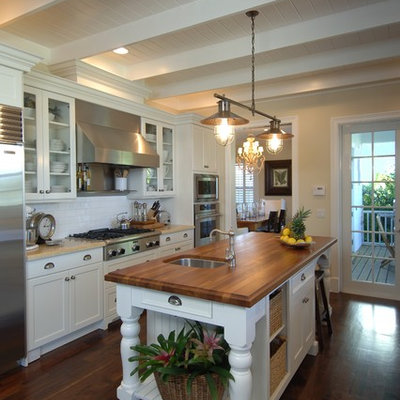 Example of a mid-sized classic galley dark wood floor enclosed kitchen design in Miami with subway tile backsplash, wood countertops, white cabinets, white backsplash, stainless steel appliances, a single-bowl sink, shaker cabinets and an island