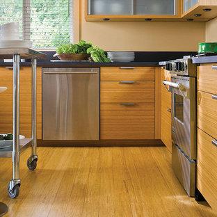 Kleine Asiatische Wohnküche in U-Form mit flächenbündigen Schrankfronten, hellen Holzschränken, Speckstein-Arbeitsplatte, Küchenrückwand in Schwarz, Küchengeräten aus Edelstahl, Bambusparkett und Kücheninsel in Chicago