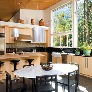 Mid-sized asian eat-in kitchen designs - Inspiration for a mid-sized asian l-shaped porcelain floor eat-in kitchen remodel in Chicago with a farmhouse sink, flat-panel cabinets, light wood cabinets, soapstone countertops, black backsplash, stone tile backsplash, stainless steel appliances and an island