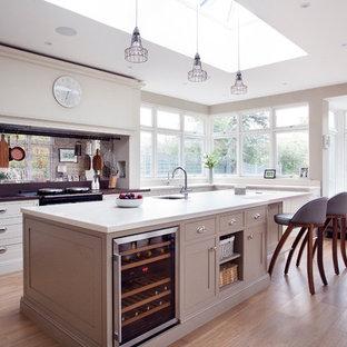 Inspiration för ett lantligt kök, med en undermonterad diskho, luckor med profilerade fronter, vita skåp, stänkskydd med metallisk yta, spegel som stänkskydd, ljust trägolv, en köksö och rostfria vitvaror