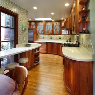 Small eclectic galley eat-in kitchen in San Francisco with raised-panel cabinets, medium wood cabinets, quartz benchtops, white splashback, glass tile splashback, medium hardwood floors, a double-bowl sink, coloured appliances and brown floor.
