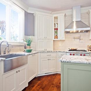 Foto på ett funkis l-kök, med rostfria vitvaror, en rustik diskho, granitbänkskiva, luckor med profilerade fronter, vita skåp, beige stänkskydd och stänkskydd i stenkakel