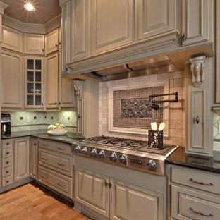 Foto på ett vintage kök, med luckor med upphöjd panel, beige skåp, beige stänkskydd och rostfria vitvaror