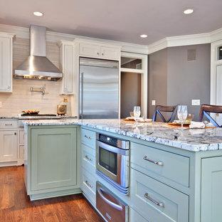 Moderne Küche mit Küchengeräten aus Edelstahl, Granit-Arbeitsplatte, Kassettenfronten, grünen Schränken und Küchenrückwand in Beige in Atlanta