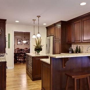 アトランタの広いトラディショナルスタイルのおしゃれなキッチン (シルバーの調理設備、アンダーカウンターシンク、レイズドパネル扉のキャビネット、濃色木目調キャビネット、御影石カウンター、ベージュキッチンパネル、石タイルのキッチンパネル、淡色無垢フローリング、茶色い床、ベージュのキッチンカウンター) の写真
