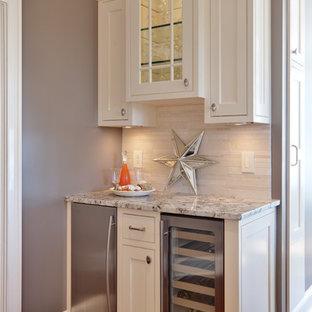 アトランタのトラディショナルスタイルのおしゃれなキッチン (シェーカースタイル扉のキャビネット、白いキャビネット、御影石カウンター、ベージュキッチンパネル、シルバーの調理設備) の写真