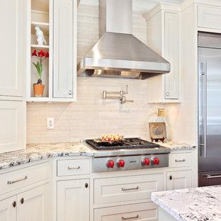 Immagine di una cucina minimal con elettrodomestici in acciaio inossidabile, top in granito, ante a filo, ante bianche, paraspruzzi beige e paraspruzzi in travertino