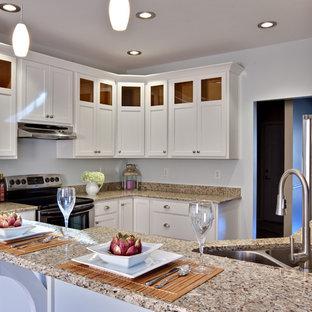 アトランタの中くらいのコンテンポラリースタイルのおしゃれなキッチン (シルバーの調理設備、御影石カウンター、ダブルシンク、白いキャビネット、シェーカースタイル扉のキャビネット、無垢フローリング、茶色い床、御影石のキッチンパネル、ベージュのキッチンカウンター) の写真