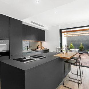 Inspiration för moderna svart kök, med en enkel diskho, släta luckor, svarta skåp, spegel som stänkskydd, svarta vitvaror, en köksö, mellanmörkt trägolv och brunt golv
