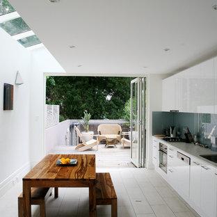 シドニーの北欧スタイルのおしゃれなキッチン (フラットパネル扉のキャビネット、白いキャビネット、青いキッチンパネル、ガラス板のキッチンパネル、シルバーの調理設備の、セラミックタイルの床) の写真
