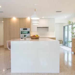 Удачное сочетание для дизайна помещения: большая угловая кухня-гостиная в стиле модернизм с раковиной в стиле кантри, плоскими фасадами, светлыми деревянными фасадами, столешницей из акрилового камня, белым фартуком, техникой из нержавеющей стали, полом из терраццо, островом, разноцветным полом и белой столешницей - самое интересное для вас