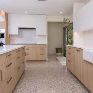 Idéer för ett stort modernt vit kök, med en rustik diskho, släta luckor, skåp i ljust trä, bänkskiva i koppar, vitt stänkskydd, rostfria vitvaror, terrazzogolv, en köksö och flerfärgat golv
