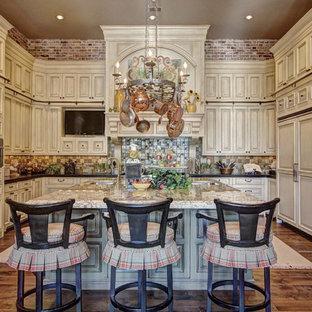 Elegant u-shaped kitchen photo in Austin with beige cabinets, multicolored backsplash and paneled appliances