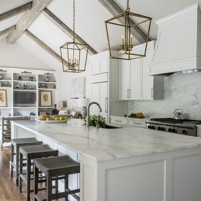 Inspiration for a timeless galley medium tone wood floor open concept kitchen remodel in Austin with a single-bowl sink, recessed-panel cabinets, white cabinets, marble countertops, white backsplash, stone slab backsplash, paneled appliances and an island