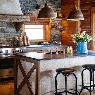 ボストンの大きいラスティックスタイルのおしゃれなキッチン (エプロンフロントシンク、シェーカースタイル扉のキャビネット、中間色木目調キャビネット、ソープストーンカウンター、グレーのキッチンパネル、石タイルのキッチンパネル、シルバーの調理設備の、無垢フローリング、茶色い床、グレーのキッチンカウンター) の写真