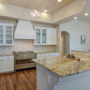 アルバカーキの中サイズのサンタフェスタイルのおしゃれなキッチン (アンダーカウンターシンク、シェーカースタイル扉のキャビネット、白いキャビネット、御影石カウンター、ベージュキッチンパネル、ガラス板のキッチンパネル、シルバーの調理設備の) の写真