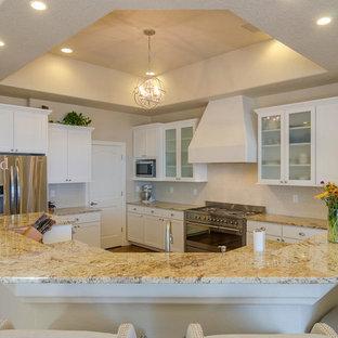 アルバカーキの中サイズのサンタフェスタイルのおしゃれなキッチン (アンダーカウンターシンク、シェーカースタイル扉のキャビネット、白いキャビネット、御影石カウンター、ベージュキッチンパネル、ガラス板のキッチンパネル、シルバーの調理設備の、濃色無垢フローリング) の写真