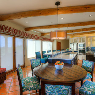 フェニックスの広いサンタフェスタイルのおしゃれなキッチン (エプロンフロントシンク、シェーカースタイル扉のキャビネット、濃色木目調キャビネット、再生ガラスカウンター、青いキッチンパネル、セラミックタイルのキッチンパネル、シルバーの調理設備、テラコッタタイルの床) の写真