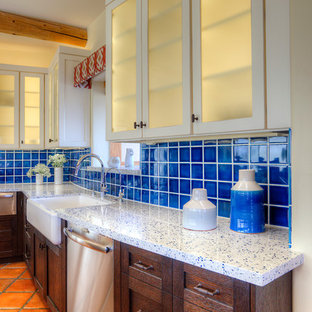 Large southwestern eat-in kitchen pictures - Example of a large southwest l-shaped terra-cotta floor eat-in kitchen design in Phoenix with a farmhouse sink, shaker cabinets, dark wood cabinets, recycled glass countertops, blue backsplash, ceramic backsplash, stainless steel appliances and an island