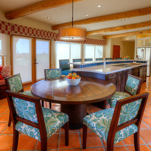 Large southwestern eat-in kitchen designs - Eat-in kitchen - large southwestern l-shaped terra-cotta floor eat-in kitchen idea in Phoenix with a farmhouse sink, shaker cabinets, dark wood cabinets, recycled glass countertops, blue backsplash, ceramic backsplash, stainless steel appliances and an island