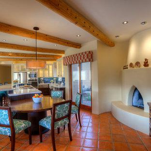 Inredning av ett amerikanskt stort kök, med en rustik diskho, skåp i shakerstil, skåp i mörkt trä, bänkskiva i återvunnet glas, blått stänkskydd, stänkskydd i keramik, rostfria vitvaror, klinkergolv i terrakotta och en köksö