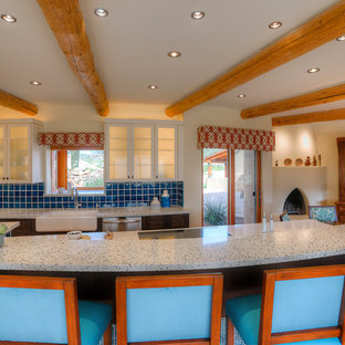 Large southwestern eat-in kitchen inspiration - Inspiration for a large southwestern l-shaped terra-cotta floor eat-in kitchen remodel in Phoenix with a farmhouse sink, shaker cabinets, dark wood cabinets, recycled glass countertops, blue backsplash, ceramic backsplash, stainless steel appliances and an island