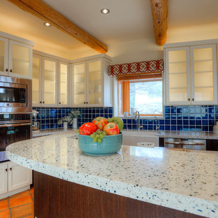 Large southwestern eat-in kitchen ideas - Large southwest l-shaped terra-cotta floor eat-in kitchen photo in Phoenix with a farmhouse sink, shaker cabinets, dark wood cabinets, recycled glass countertops, blue backsplash, ceramic backsplash, stainless steel appliances and an island